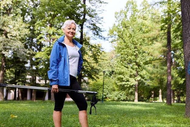 Concepto de salud, bienestar, vitalidad, recreación y actividad vista de verano al aire libre de una elegante y segura mujer de sesenta años posando contra pinos, sosteniendo un bastón nórdico y sonriendo