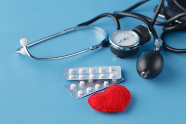 Concepto de salud del corazón, corazón de juguete y thonometer en azul