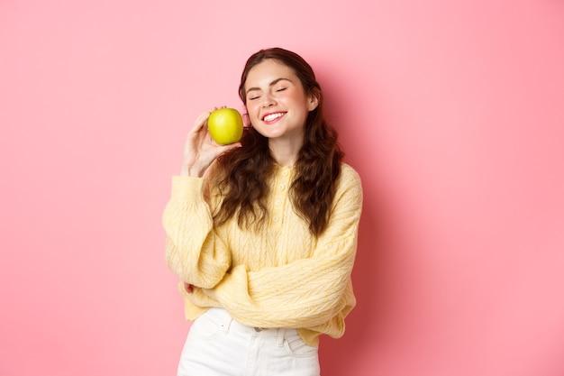 Concepto de salud, estomatología y personas. niña feliz muestra sus dientes blancos perfectos, sonrisa y manzana verde, comiendo alimentos saludables y frutas, de pie contra la pared rosa