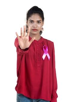 Concepto de salud y medicina - manos de mujer joven sosteniendo cinta rosa de concienciación sobre el cáncer de mama