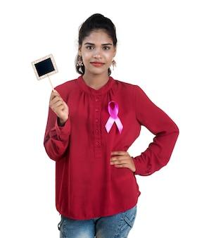 Concepto de salud y medicina: manos de mujer joven sosteniendo una cinta rosada de concienciación sobre el cáncer de mama y una pequeña pizarra negra