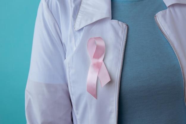 Concepto de salud y medicina - mujer en camiseta en blanco con cinta rosa de concienciación sobre el cáncer de mama