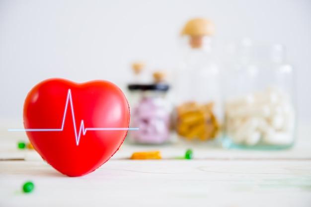 Concepto de salud y médico. corazón rojo en la mesa de madera con un conjunto de frascos de medicamentos y píldoras medicinales
