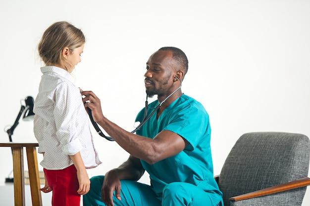 Concepto de salud y médico - médico con estetoscopio escuchando cofre infantil en el hospital