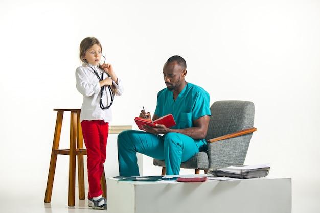 Concepto de salud y médico - médico y niña con estetoscopio en el hospital