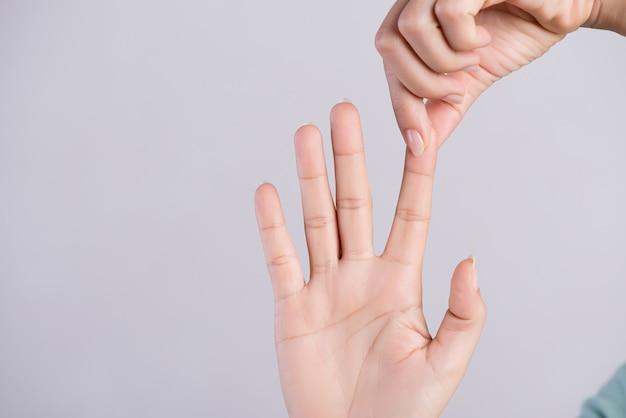 Concepto de salud y médico. mujer masajeando su dedo índice doloroso