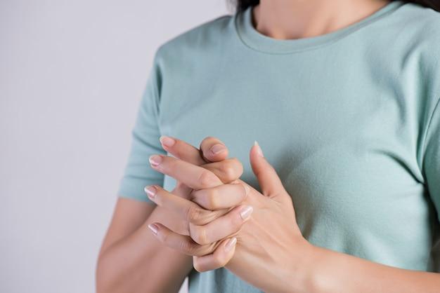 Concepto de salud y médico. primer plano de mujer grietas nudillos