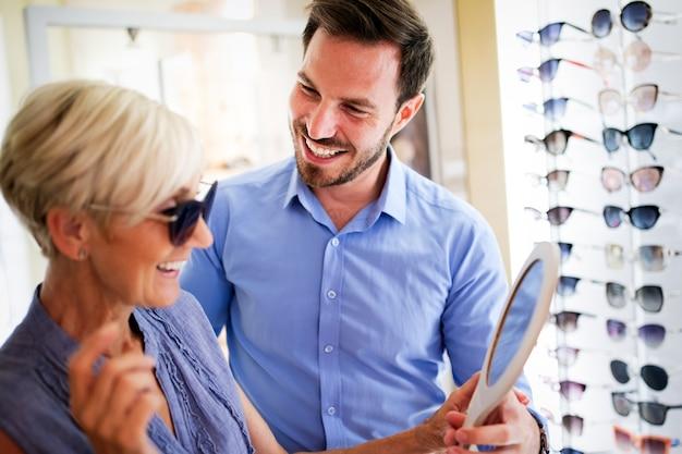 Concepto de salud, personas, vista y visión. mujer mayor con hombre óptico eligiendo gafas en la tienda de óptica