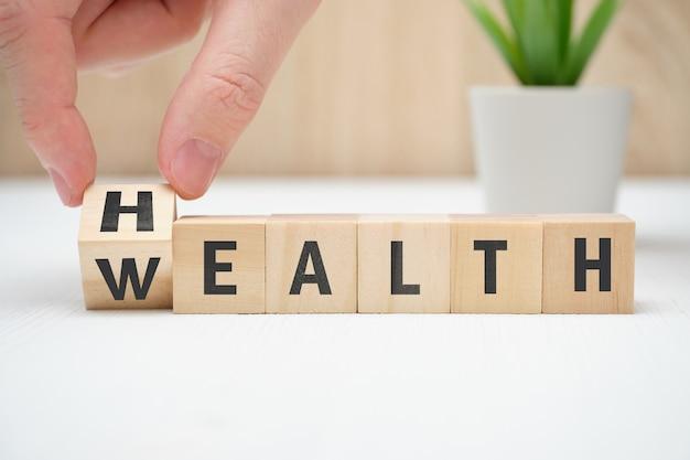 Concepto salud riqueza en bloque de madera de la mano.