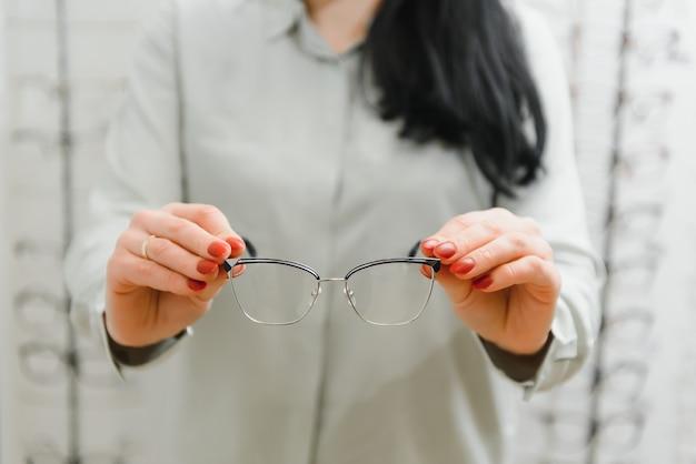 Concepto de salud, vista y visión - mujer feliz eligiendo gafas en la tienda de óptica