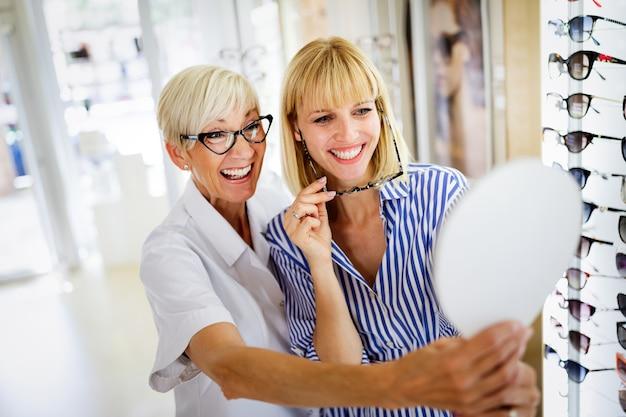 Concepto de salud, vista y visión. mujer joven feliz eligiendo gafas en la tienda de óptica