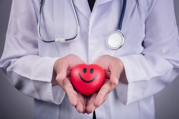 Concepto saludable - bola roja del corazón en la mano de un médico y un estetoscopio azul
