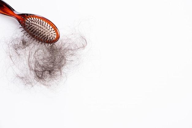 Concepto saludable cepillo con cabello dañado larga perdida en blanco