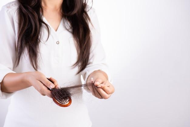 Concepto saludable mujer muestra su cepillo con cabello dañado de larga pérdida