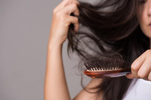 Concepto saludable la mujer muestra su pincel con cabello de larga pérdida y mirando su cabello.