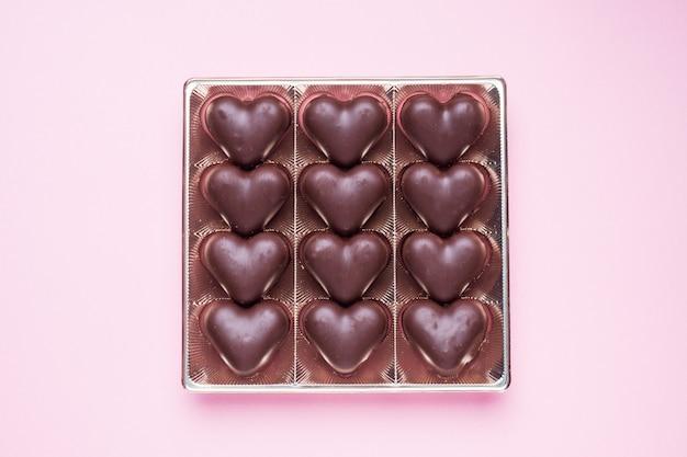 Concepto de san valentín. caramelos de chocolate, corazones sobre un fondo rosa