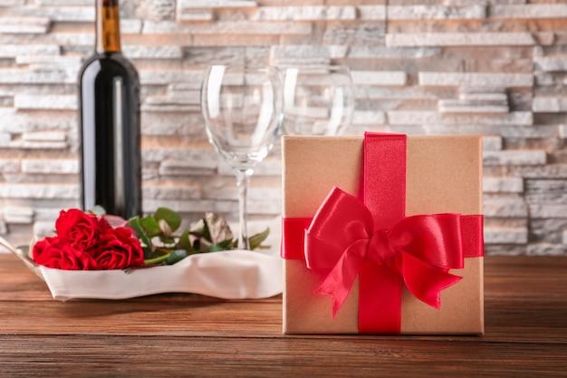 Concepto de san valentín. vino, rosas y caja de regalo en mesa de madera