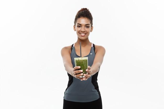 Concepto sano y de la aptitud - señora africana americana hermosa en la ropa de la aptitud que bebe la bebida vegetal sana. aislado en el fondo blanco.