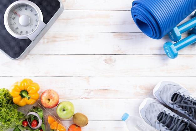 Concepto sano de la forma de vida, de la comida y del deporte en el fondo de madera blanco.