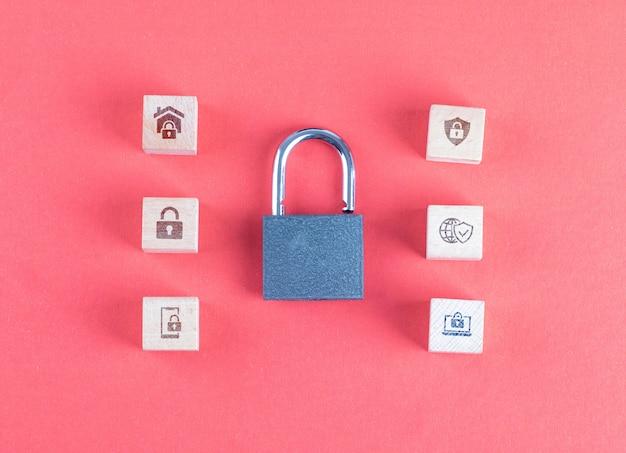 Concepto de seguridad con cerradura, iconos en cubos de madera en mesa rosa plana lay