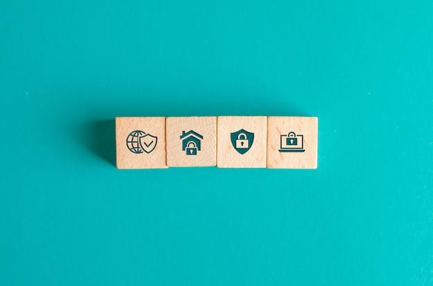 Concepto de seguridad con iconos en bloques de madera en mesa turquesa endecha plana.