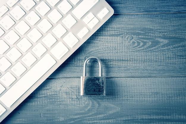 Concepto de seguridad informática. candado desbloqueado en el teclado del portátil. símbolo seguro. el enfoque selectivo en la mesa de madera gris