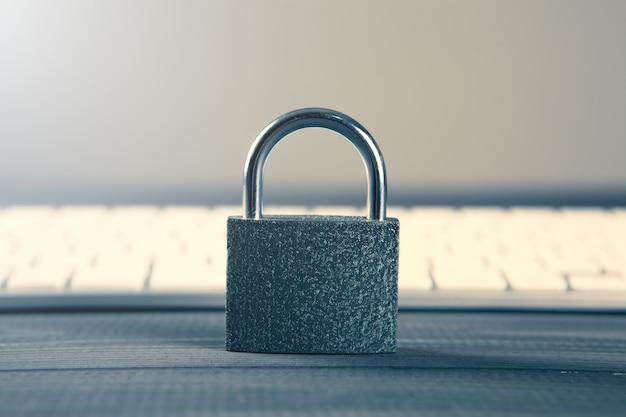 Concepto de seguridad informática. candado desbloqueado en el teclado del portátil. símbolo seguro. el enfoque selectivo en la mesa de madera gris Foto Premium