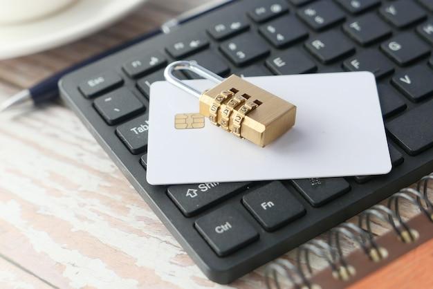 Concepto de seguridad en internet con candado y tarjeta de crédito en el teclado de la computadora