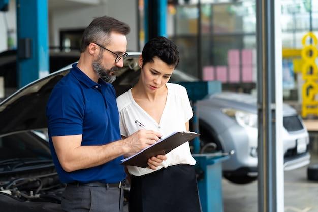 Concepto de seguro de automóvil. el agente de seguros examina el automóvil dañado con la clienta y escribe la información en el formulario de informe de reclamación.