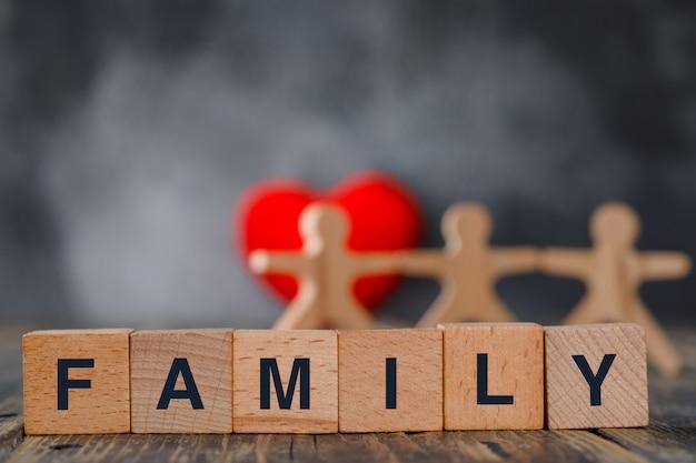 Concepto de seguro familiar con figuras de madera de personas, cubos, vista lateral de corazón rojo.