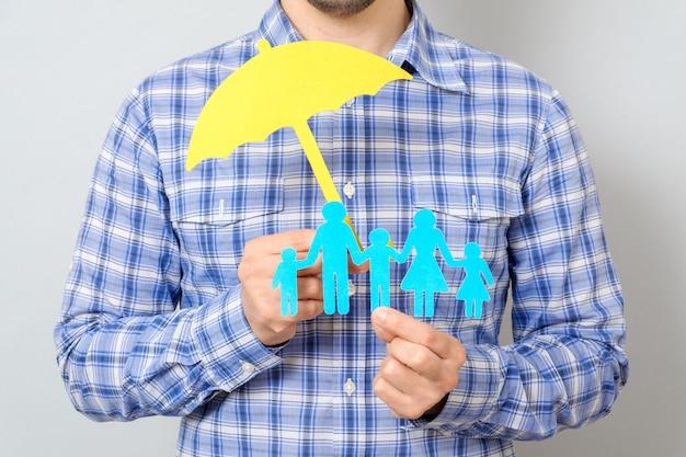 Concepto de seguro familiar con paraguas protegiendo a una familia
