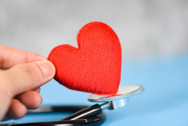 Concepto de seguro de salud: estetoscopio y atención médica del corazón rojo sobre fondo azul