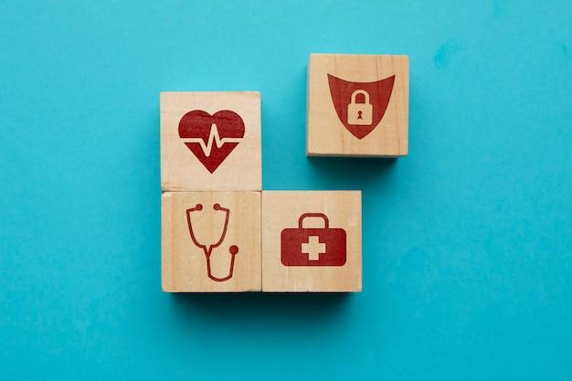 Concepto de seguro de salud con iconos en bloques de madera.