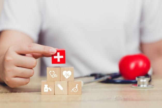 Concepto de seguro de salud, mano arreglando apilado de bloques de madera con un icono de atención médica