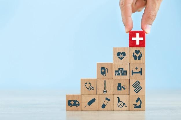 Concepto de seguro de salud, mano arreglando el apilamiento de bloques de madera con icono de atención médica.