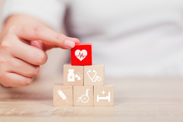 Concepto de seguro de salud, mano arreglando el apilamiento de bloques de madera con el icono de atención médica.
