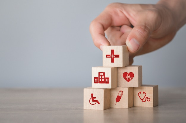 Concepto de seguro de salud, mano arreglando el apilamiento de bloques de madera con el icono de salud médica.