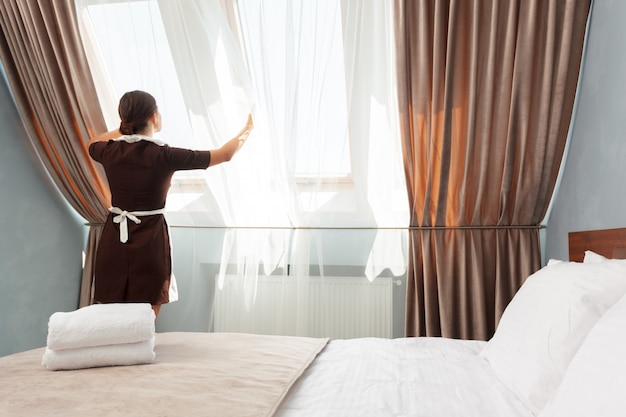 Concepto de servicio de hotel. camarera de ajuste de cortinas en la habitación.