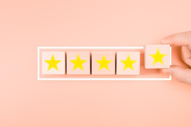 Concepto de servicios de excelente calificación. mano poniendo el bloque de madera en forma de cinco estrellas de oro del cubo en la mesa de madera de fondo rosa