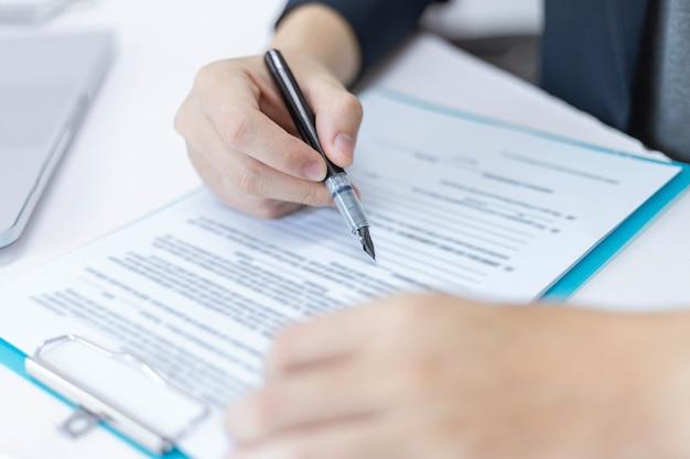 Concepto de socios comerciales un joven empresario sosteniendo un bolígrafo apuntando al resumen de ganancias del mes reciente que se muestra en formularios de documentos.