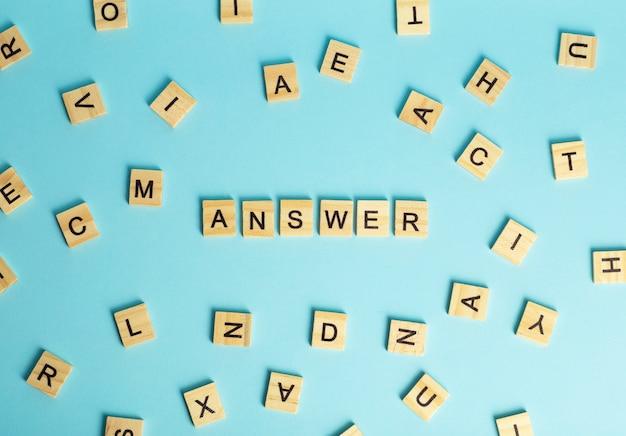 Concepto de solución de preguntas y respuestas. la palabra respuesta compuesta de un montón de letras diferentes sobre un fondo azul.