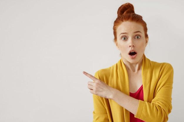 Concepto de sorpresa y asombro. sentimientos humanos y reacción. retrato de mujer de jengibre caucásica joven sorprendida sorprendida señalando con el dedo índice hacia los lados