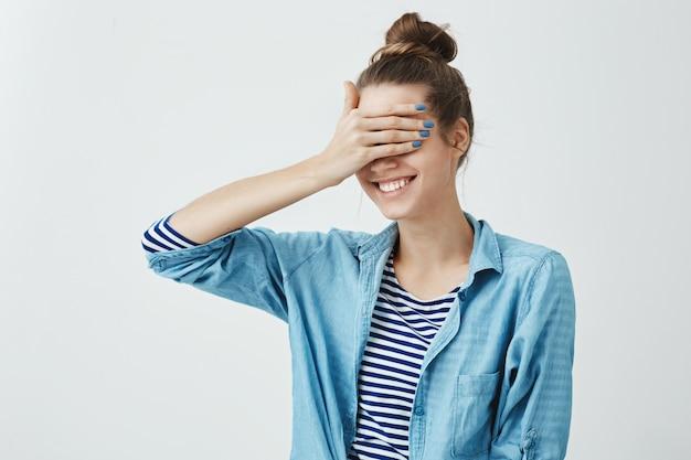 Concepto de sorpresa y sentimientos. retrato de encantadora mujer caucásica linda con peinado de moño cubriendo los ojos con la palma y sonriendo con emoción, deseando ver lo que está sucediendo