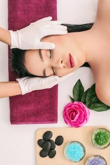 Concepto de spa, belleza, cuidado de las personas y el cuerpo: hermosa mujer recibiendo tratamiento facial
