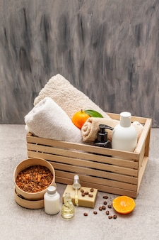 Concepto de spa de café y mandarina. toallas, aceite, exfoliante, jabón, loción. ingrediente natural, caja de madera.