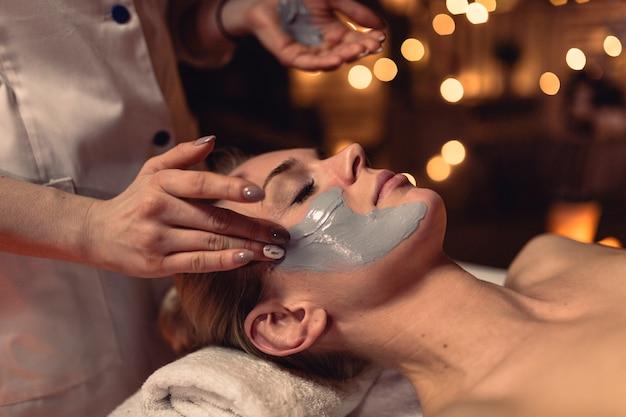 Concepto de spa con mujer con crema en la cara