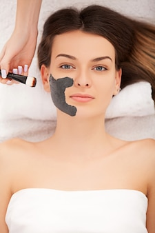 Concepto de spa. mujer joven con máscara facial de nutrientes en el salón de belleza, de cerca