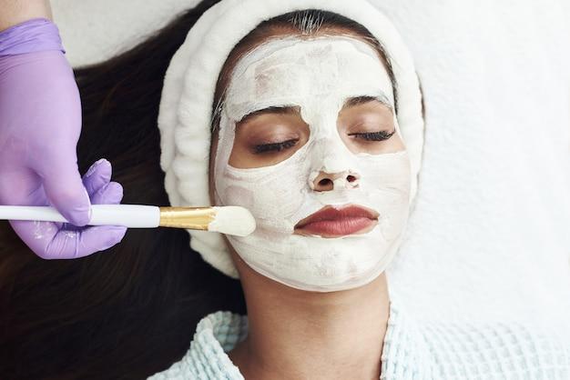 Concepto de spa. mujer joven con mascarilla facial nutritiva en salón de belleza, de cerca.