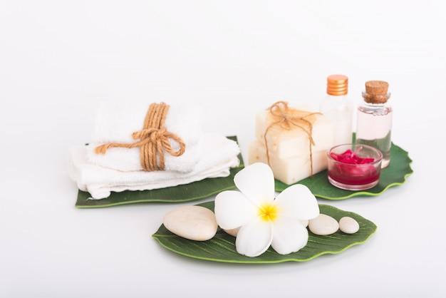 Concepto de spa, piedra blanca, vela roja, jabón líquido de rosas, toalla, flores en hojas verdes