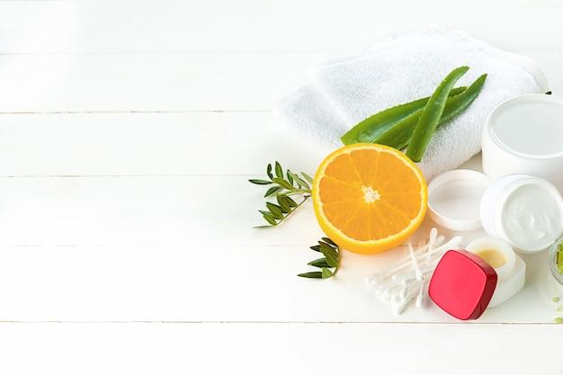 Concepto de spa con sal, menta, loción, toalla sobre fondo blanco.